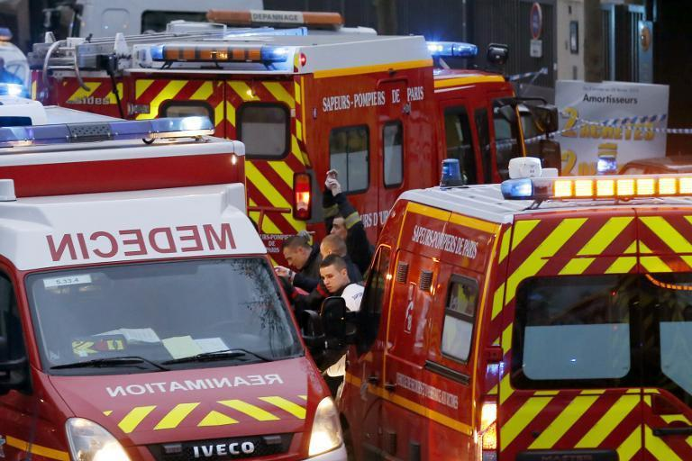 Firefighters and rescue workers gather at the site of a shooting in Montrouge, south of Paris