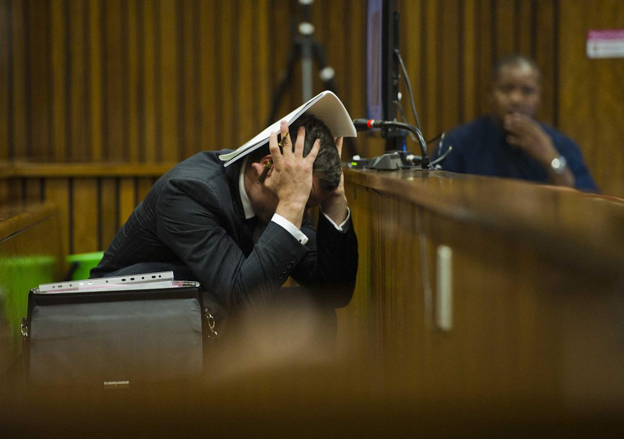 Oscar Pistorius covers his head with his hands and a notebook as he listens to forensic evidence during his trial in court in Pretoria, South Africa, Thursday March 13, 2014. Pistorius is charged with the shooting death of his girlfriend Reeva Steenkamp on Valentines Day in 2013. (AP Photo/Alet Pretorius, Pool)