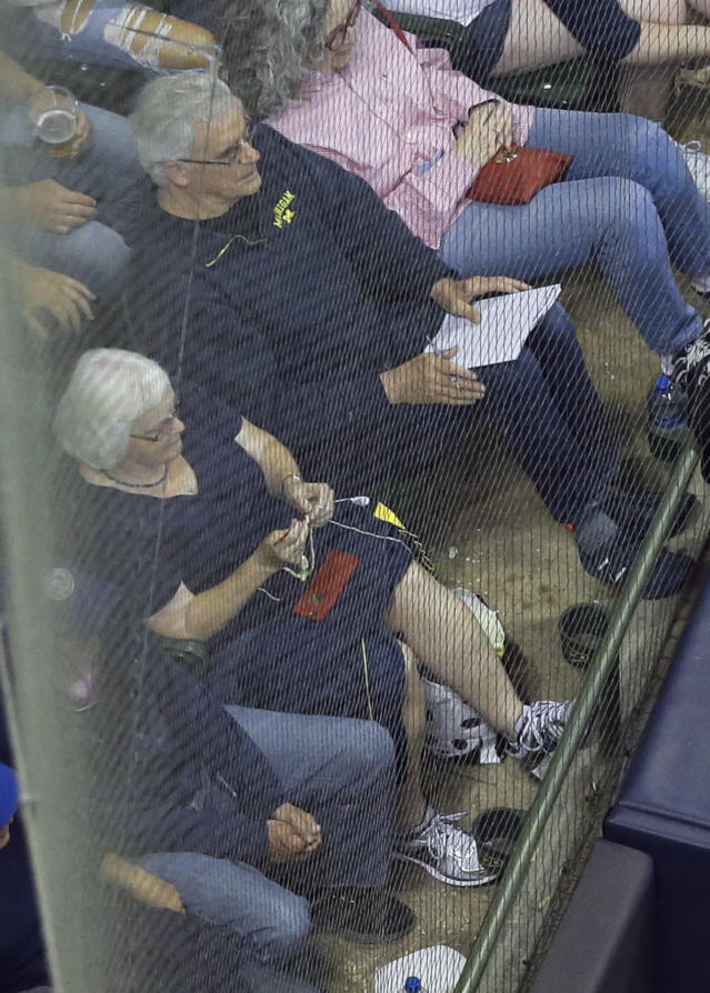 A woman sitting in the front row behind home plate crochets during a baseball game between the St. Louis Cardinals and the Milwaukee Brewers on Friday, June 22, 2018, in Milwaukee. The fan barely reacted when Milwaukee's Jesus Aguilar homered to break up a no-hitter by St. Louis' Jack Flaherty in the seventh inning. The Brewers won 2-1. (AP Photo/Morry Gash)