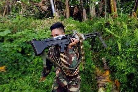 A Philippines army soldier runs with a machine gun in Marawi city, Philippines June 28, 2017. REUTERS/Jorge Silva