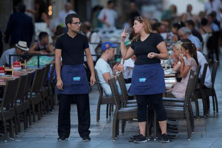 FILE PHOTO: A waitress and a waiter chat as they wait for customers at the terrace of a restaurant in downtown Ronda, southern Spain August 31, 2018. REUTERS/Jon Nazca/File Photo