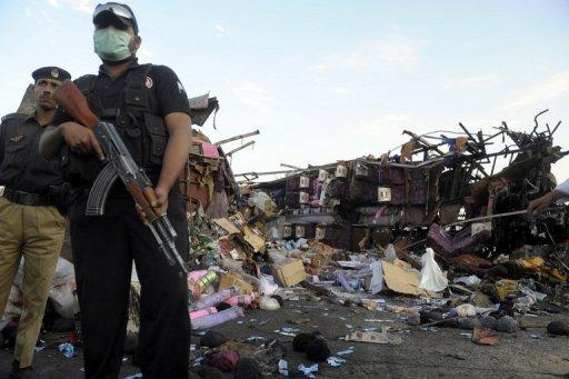 Pakistani security personnel stand guard next to wreckage of a destroyed bus near Quetta