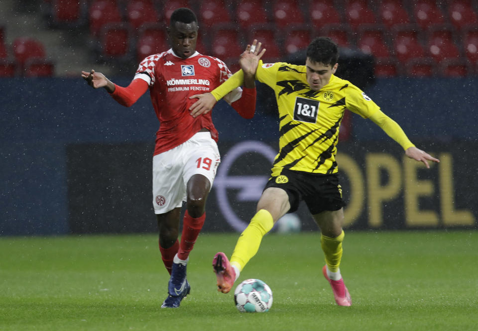 Mainz's Moussa Niakhate, left, vies for the ball with Dortmund's Giovanni Reyna during the German Bundesliga soccer match between FSV Mainz 05 and Borussia Dortmund in Mainz, Germany, Sunday, May 16, 2021. (AP Photo/Michael Probst,Pool)