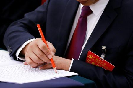 A delegate marks a passage in a text during a session on the second day of the 19th National Congress of the Communist Party of China of the Great Hall of the People in Beijing, October 19, 2017. REUTERS/Thomas Peter