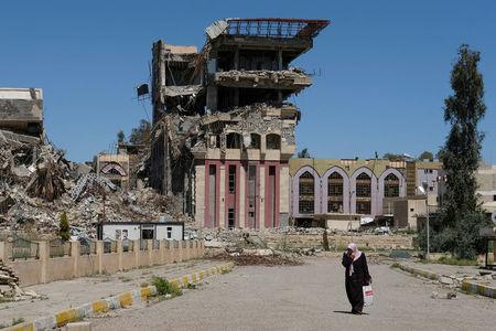 A woman walks in front of the remains of the University of Mosul, which was burned and destroyed during a battle with Islamic State militants, in Mosul