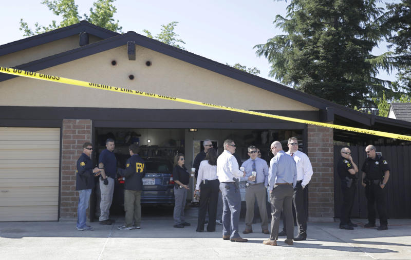 "FILE - In this April 25, 2018 file photo, authorities gather outside the home of Joseph James DeAngelo in Citrus Heights, Calif. The home of DeAngelo, suspected of being the notorious ""Golden State Killer"", has been sold to a couple who intend to live there. The Sacramento Bee reports DeAngelo's 1,500-square-foot home in Citrus Heights, Calif., was sold last month. (AP Photo/Rich Pedroncelli,File)"