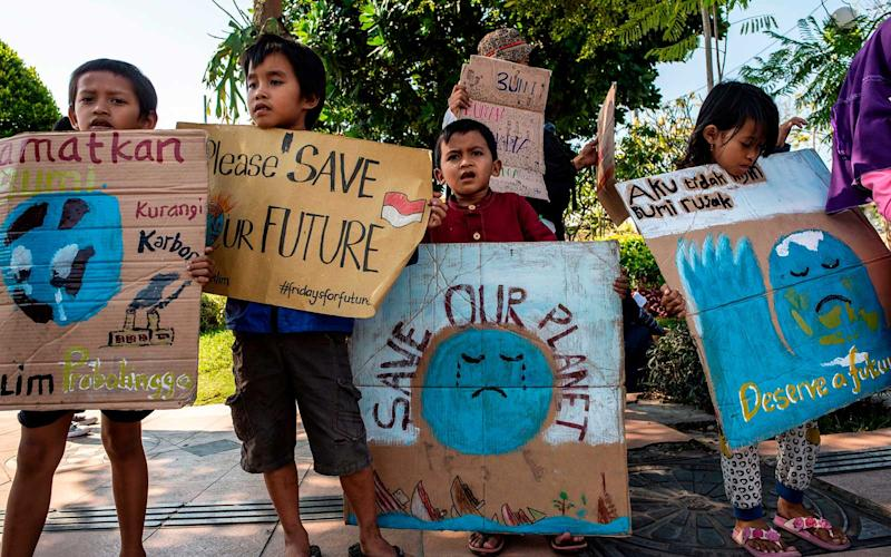 A group of Indonesians hold placards as they take part in a global climate change campaign in Surabaya on September 20, 2019. | JUNI KRISWANTO/Getty Images
