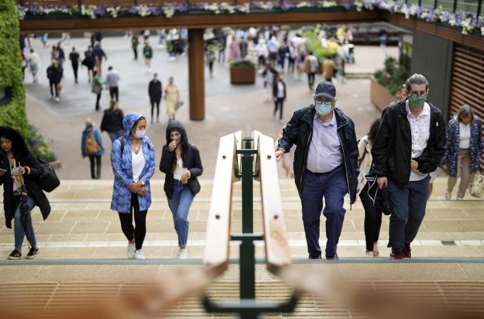 People walk around the grounds on day one of the Wimbledon Tennis Championships in London, Monday June 28, 2021. (AP Photo/Alberto Pezzali)