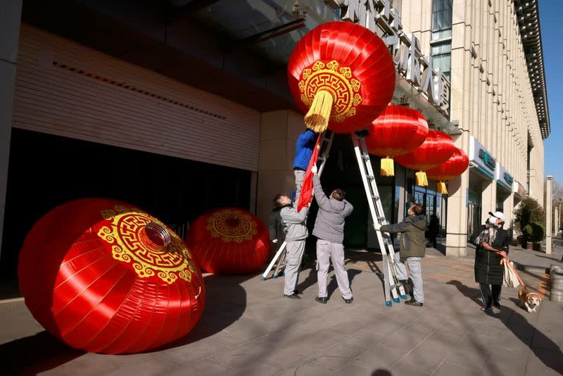 Men hang red lanterns marking New Year and Lunar New Year festivities following the outbreak of the coronavirus disease (COVID-19) in Beijing