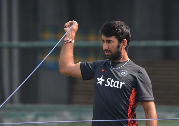 Indian cricketer Cheteshwar Pujara stretches during a team training session at the Sher-e-Bangla National Cricket Stadium in Dhaka on February 24, 2014. AFP PHOTO/Munir uz ZAMAN (Photo credit should read MUNIR UZ ZAMAN/AFP/Getty Images)