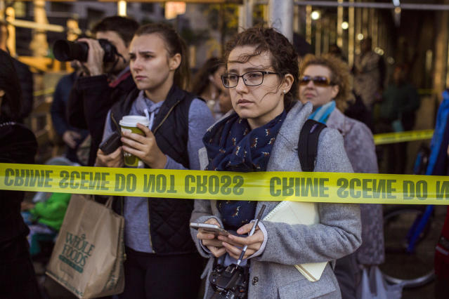 <p>People and media watch the scene after a motorist drove onto a busy bicycle path near the World Trade Center memorial and struck several people, Oct. 31, 2017, in New York. (Photo: Andres Kudacki/AP) </p>