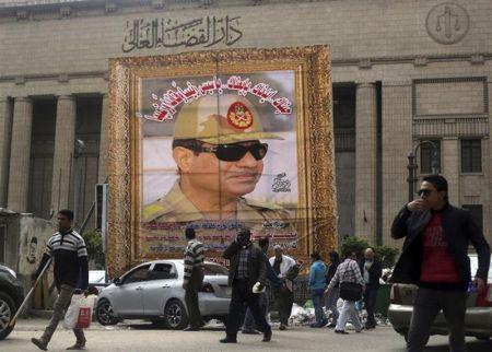People walk past a huge banner for Egypt's army chief, Field Marshal Abdel Fattah al-Sisi in front of the High Court of Justice in downtown Cairo, March 13, 2014