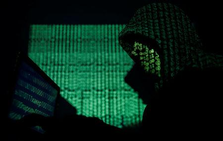 Hooded man holds a laptop computer as cyber code is projected on him in this illustration picture