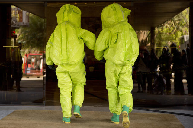 Police officers wearing chemical protection suits attend a simulation of a chemical attack, in preparation for any extreme situations during the upcoming World Cup, in Sao Paulo, Brazil, Tuesday, March 25, 2014. (AP Photo/Andre Penner)