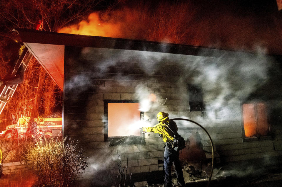 A firefighter sprays water on a burning home as the Mountain View Fire tears through the Walker community in Mono County, Calif., on Wednesday, Nov. 18, 2020. (AP Photo/Noah Berger)