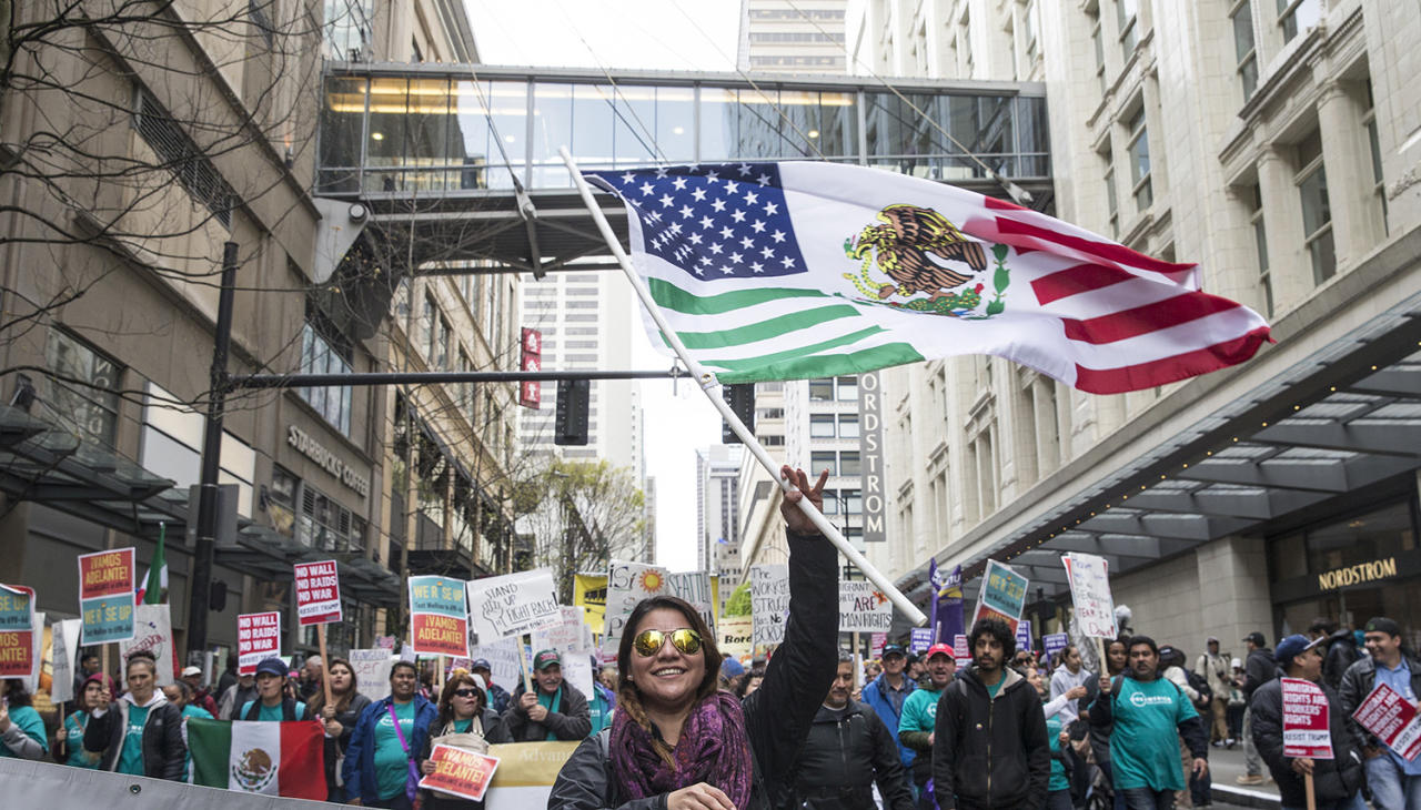 <p>Jennifer Molina waves a flag while walking through downtown during the Workers and Immigrant Rights March, May 1, 2017, in Seattle. Hundreds took part in the annual May Day event. (Stephen Brashear/Getty Images) </p>