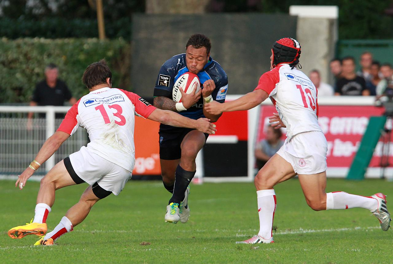 Montpellier's Anthony Tuitavake, centre, is tackled by Biarritz's Daniel Waenga , right, and Biarritz's Charles Gimenez, left, during their French Top 14 rugby union match at the Stade Aguilera, in Biarritz, southwestern France, Saturday Aug. 24, 2013. (AP Photo/Bob Edme)