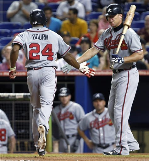 Atlanta Braves' Chipper Jones, right, congratulates Michael Bourn (24) after Bourn scored on a sacrifice fly by Jason Heyward during the first inning of a baseball game against the Miami Marlins, Wednesday, Sept. 19, 2012, in Miami. (AP Photo/Wilfredo Lee)