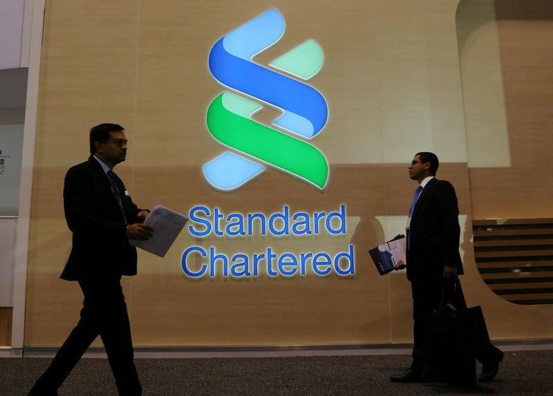 People pass by the logo of Standard Chartered plc at the SIBOS banking and financial conference in Toronto