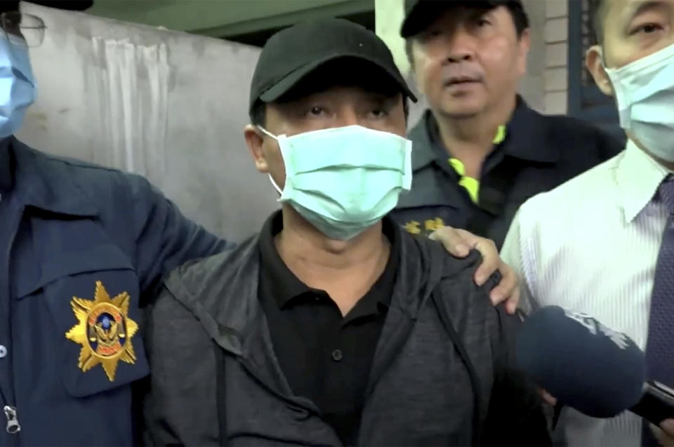 In this image taken from video, Lee Yi-hsiang, the driver of the truck that caused the train accident on Saturday, offers a public apology as he is led by police Sunday, April 4, 2021, in Hualien, Taiwan. Lee's truck slid into the path of an oncoming train, causing Taiwan's worst railway accident in decades that which killed dozens of people, and injuring hundreds more. (EBC via AP)