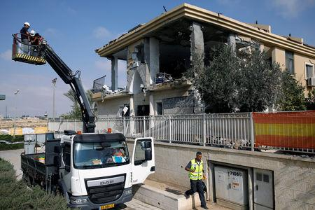Israeli sappers stand on a crane as they work on a house that the Israeli military said was hit by a rocket fired from the Gaza Strip, in Beersheba, southern Israel October 17, 2018. REUTERS/Amir Cohen
