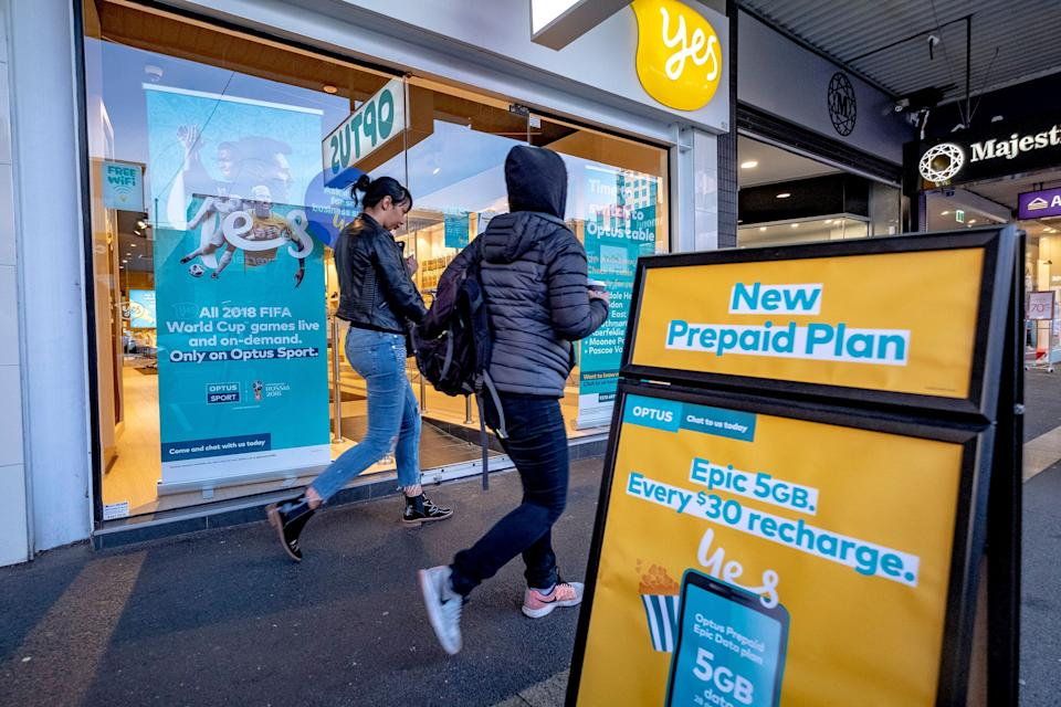 People walk past an Optus store in Melbourne. Picture: AAP Image/Luis Ascui