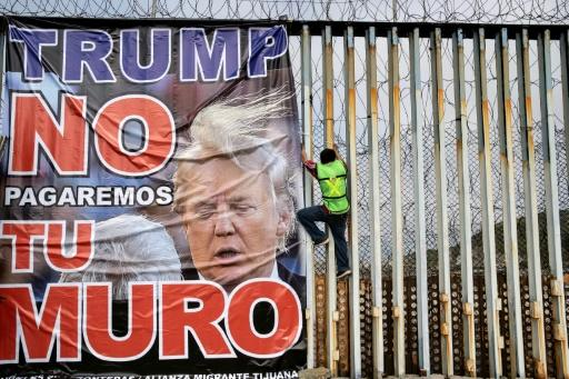 "A protestor against the wall on the US-Mexico frontier hangs a banner reading ""Trump we will not pay for your wall"" at Playas de Tijuana, Mexico, on February 2, 2020"
