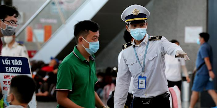A staff member (R) from Vietnam's Centre of Disease Control assists passengers wearing face masks as they queue up for temperature checks at the departures terminal at Danang's international airport on July 27, 2020. (Photo by Hoang Khanh / AFP) (Photo by HOANG KHANH/AFP via Getty Images)
