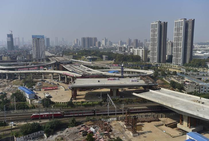 An overpass is seen under construction as a train travels past in Wuhan