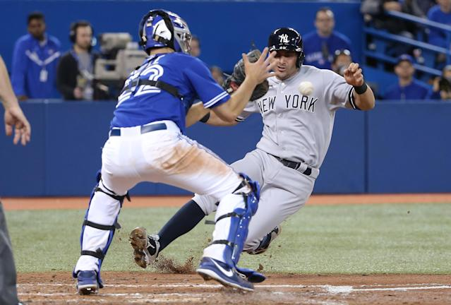 TORONTO, CANADA - APRIL 5: Josh Thole #22 of the Toronto Blue Jays prepares to tag out Francisco Cervelli #29 the New York Yankees in the third inning during MLB game action on April 5, 2014 at Rogers Centre in Toronto, Ontario, Canada. (Photo by Tom Szczerbowski/Getty Images)