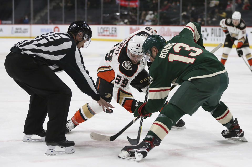 Linesman Ryan Galloway (82) drops the puck for faceoff between Anaheim Ducks' Sam Carrick (39) and Minnesota Wild's Nick Bonino (13) during the second period of an NHL hockey game Friday, May 7, 2021, in St. Paul, Minn. (AP Photo/Stacy Bengs)
