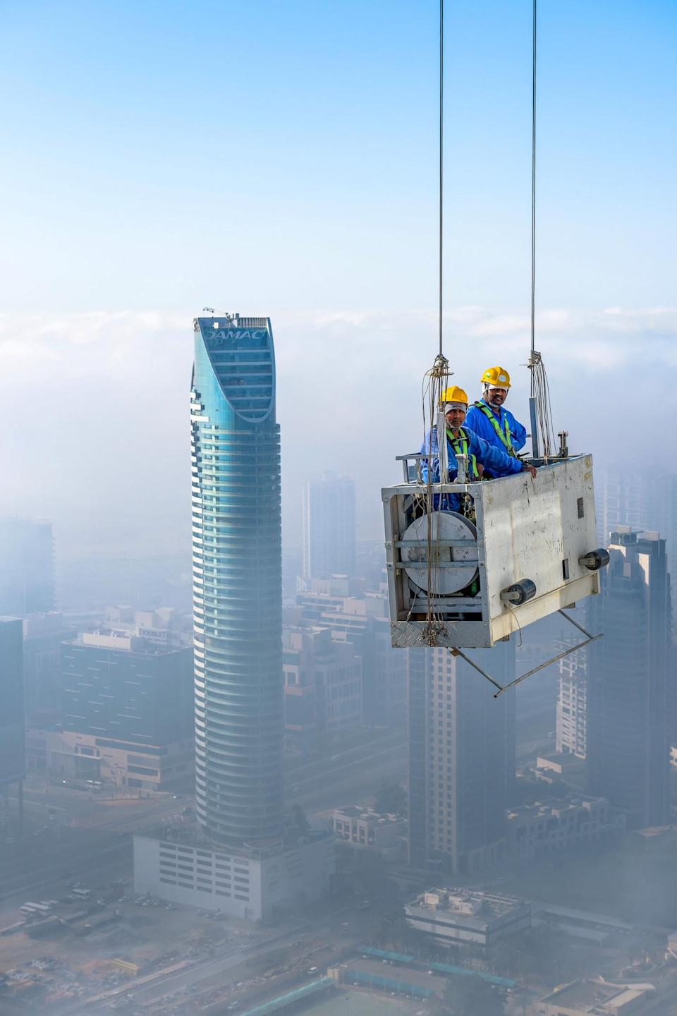 The workmen show no signs of fear as they dangle in a crib suspended by two cords 900ft above the street below. (SWNS)