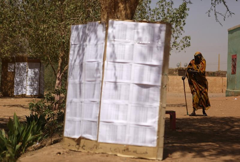 A Sudanese woman walks past a list of voters at a polling station in Khartoum's southern suburb of Mayo on April 14, 2015 (AFP Photo/Patrick Baz)