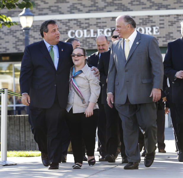 New Jersey Gov. Chris Christie walks with Lauren Sweeney, daughter of New Jersey Senate President Stephen Sweeney, right, D-Thorofare, N.J., at Gloucester County College before they broke-ground on an adult center for transition facility in Sewell, N.J., Monday, Oct. 21, 2013. Earlier Monday, Christie dropped his appeal to legalized same-sex marriages in New Jersey. In an email, the governor's office says it submitted a formal withdrawal to the state Supreme Court Monday morning. Last month, a lower-court judge ruled that New Jersey must recognize gay marriages starting Monday. Gay couples began exchanging vows shortly after midnight. (AP Photo/Mel Evans)