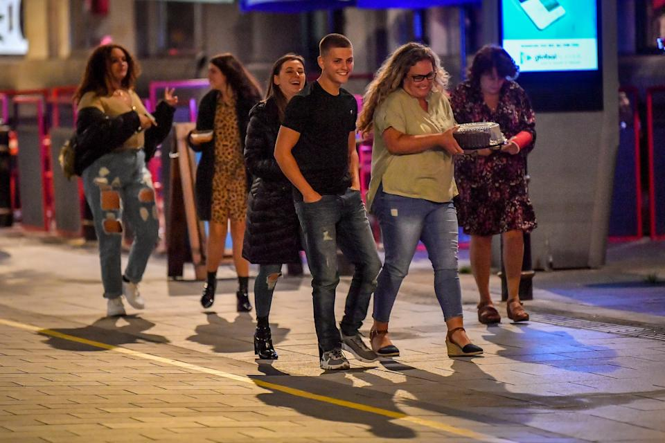 A group of young people walk through Cardiff city centre at night. A ban on groups of more than six people meeting indoors in Wales, including pubs and restaurants, is expected to be announced later today as ministers try to tackle the rising number of coronavirus cases across the UK.