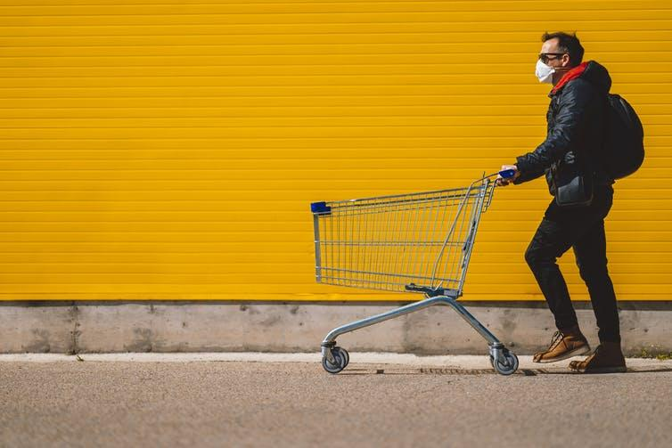 A man in a mask pushing a shopping trolley