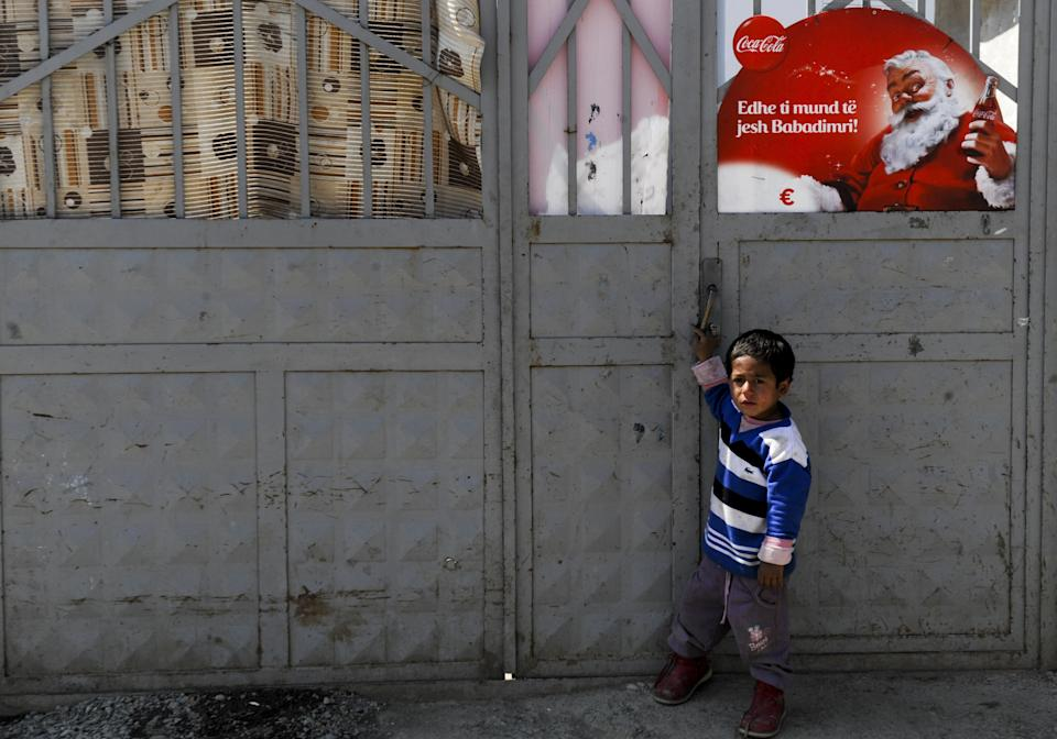 A Roma child stands in front of a shelter bearing an image of Santa Claus as advertised by Coca-Cola — which is largely credited with popularizing the modern-day image of him as a jolly white man, seen all over the world. (Photo: ARMEND NIMANI/AFP via Getty Images)