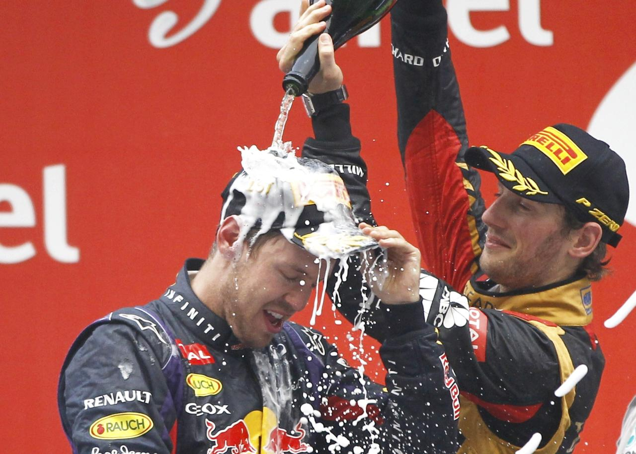 Lotus F1 Formula One driver Romain Grosjean of France (R) sprays Red Bull Formula One driver Sebastian Vettel of Germany after the Indian F1 Grand Prix at the Buddh International Circuit in Greater Noida, on the outskirts of New Delhi, October 27, 2013.  Vettel became Formula One's youngest four-times world champion on Sunday after winning the Indian Grand Prix for Red Bull. REUTERS/Adnan Abidi (INDIA - Tags: SPORT MOTORSPORT F1)