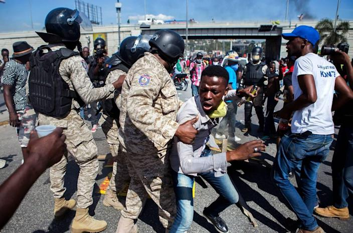 Police officers prevent a protester from fueling a burning barricade during a demonstration demanding the resignation of President Jovenel Moïse, in Port-au-Prince, Haiti, Friday, Jan. 15, 2021.