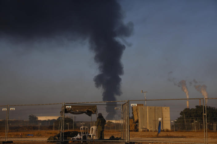 An Israeli soldier stands guard next to an Iron Dome air defense system as smoke rises from an oil tank on fire after it was hit by a rocket fired from Gaza Strip, near the town of Ashkelon, Israel, Wednesday, May 12, 2021. (AP Photo/Ariel Schalit)
