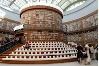 <p>A central circular pillar housed thousands of books with guest seated on the stairs to view the show.</p>