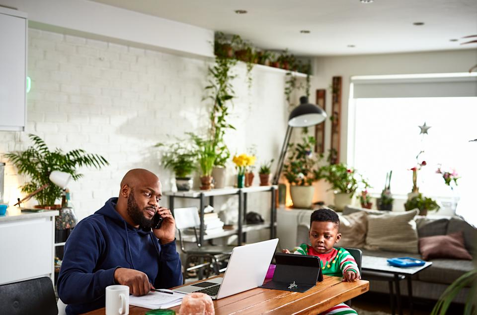 Mid adult man using phone at dining room table with laptop, boy sitting patiently with device, working from home, childcare issues, multi tasking
