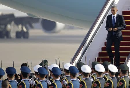 U.S. President Barack Obama steps from Air Force One to pass an honour guard upon his arrival in Beijing, November 10, 2014. REUTERS/Jason Lee