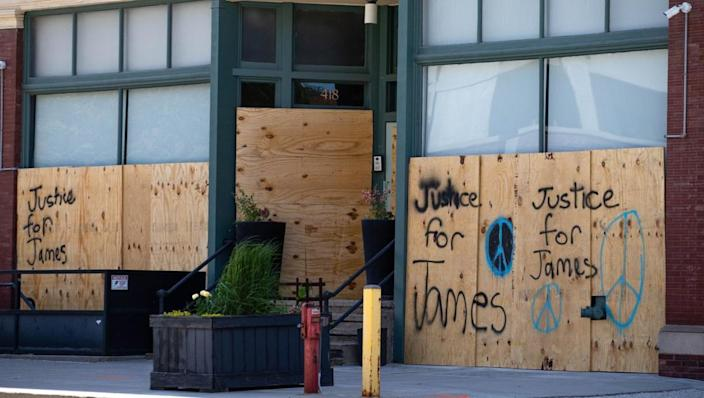 Messages for James Scurlock are spray painted on boarded up windows Monday in downtown Omaha. (Z Long/The World-Herald)