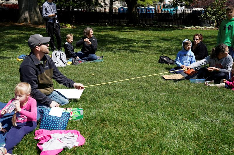 Demonstrators measure out a 'social distance' of six feet as they gather in opposition to Virginia's stay-at-home order and business closures in the wake of the coronavirus disease (COVID-19) outbreak during a protest against the lockdown measures in Richmond, Virginia, U.S., April 16, 2020. REUTERS/Kevin Lamarque TPX IMAGES OF THE DAY