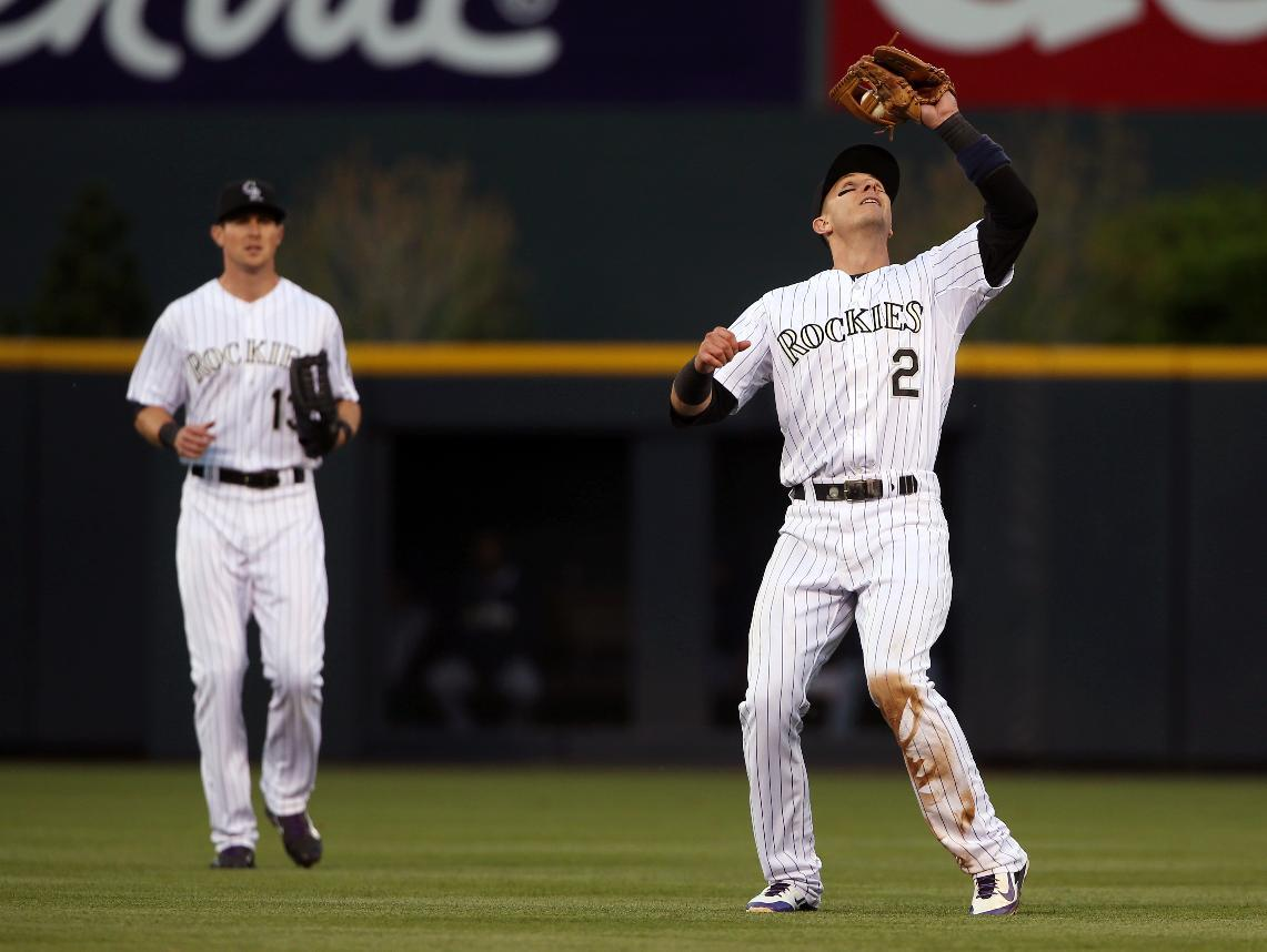 Colorado Rockies shortstop Troy Tulowitzki, front, fields pop up off the bat of San Diego Padres' Jedd Gyorko as Rockies centerfielder Drew Stubbs comes in to cover in the fifth inning of a baseball game in Denver on Saturday, May 17, 2014. (AP Photo/David Zalubowski)