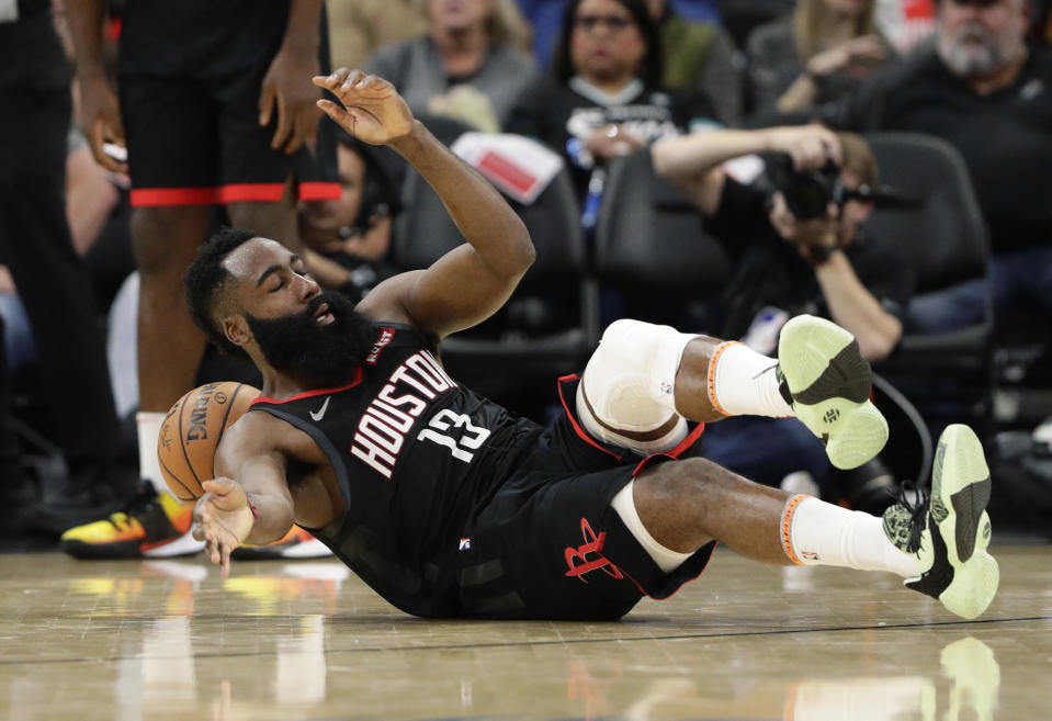 Houston Rockets guard James Harden (13) hits the court after he was fouled during the second half of an NBA basketball game against the San Antonio Spurs, in San Antonio, Tuesday, Dec. 3, 2019. San Antonio won 135-133 in double overtime. (AP Photo/Eric Gay)