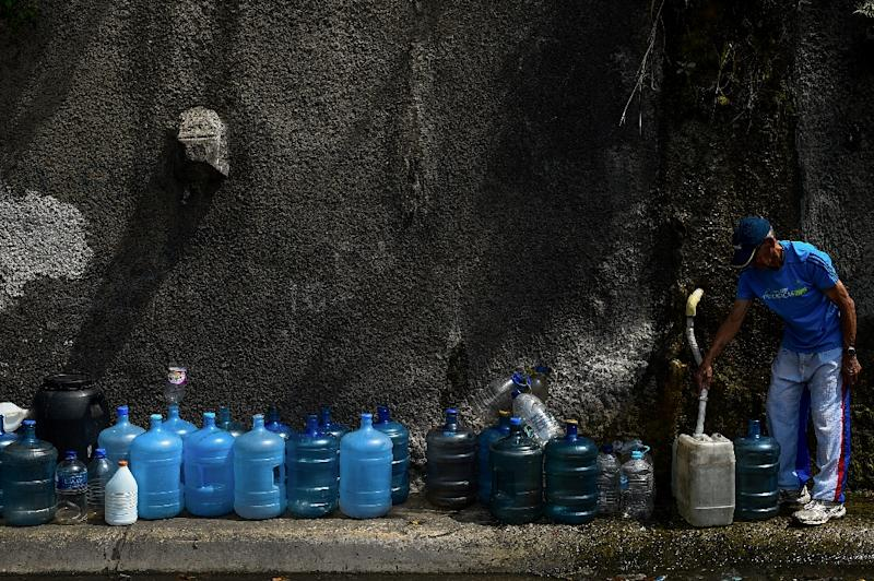 A man fills containers with water flowing down from the Wuaraira Repano mountain in Caracas -- a move necessitated by a blackout that left millions without running water (AFP Photo/FEDERICO PARRA)