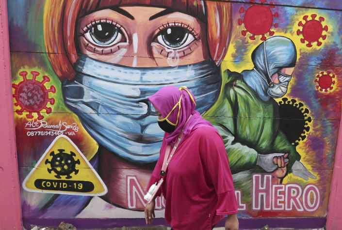 A woman walks past a coronavirus-themed mural honoring health workers in Tangerang, Indonesia, Tuesday, Jan. 26, 2021. Indonesia has reported more cases of the virus than any other countries in Southeast Asia. (AP Photo/Tatan Syuflana)