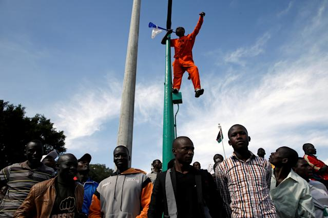 <p>A supporter of Kenyan opposition leader Raila Odinga of the National Super Alliance (NASA) coalition stands on a pole as he blows a horn ahead of his planned swearing-in ceremony as the President of the People's Assembly in Nairobi, Kenya, Jan. 30, 2018. (Photo: Baz Ratner/Reuters) </p>
